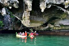 Turister i kanoter runt om Khao Phing Kan arkivfoto