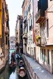 Turister i liten kanal för gondoler i den Venedig staden Royaltyfria Bilder