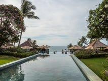 Turister i oändlighetspöl med havbakgrund i Bali arkivfoton