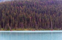 Turister i röda kanoter i Banff royaltyfri fotografi