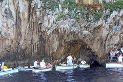 Turister i små fartyg som väntar för att skriva in den blåa grottan på Capr Royaltyfri Fotografi
