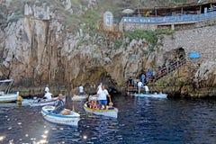 Turister i små fartyg som väntar för att skriva in den blåa grottan på Capr Arkivfoto