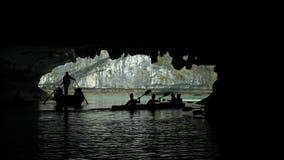 Turister i traditionella lokala fartyg och kajaker som undersöker grottorna av kalkstenöarna av mummel skäller länge, Vietnam lager videofilmer