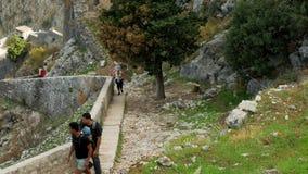 Turister klättrar trappan upp kullen till den gamla fästningen arkivfilmer