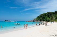 Turister kopplar av på den idylliska tropiska stranden Royaltyfri Bild