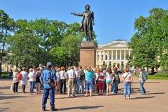 Turister lyssnar till en turnera runt om monumentet till A S Pushkin nolla Royaltyfri Fotografi