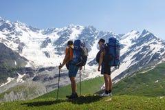 Turister med att fotvandra vandrar på bakgrunden av ett stenigt snöberg på en klar sommardag Fotvandra i berg med vänner Royaltyfri Fotografi