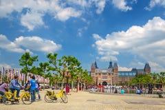 Turister med cyklar som är främsta av Rijksmuseumen i Amsterdam, Royaltyfria Bilder