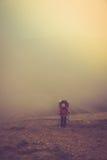 Turister med ryggsäckar klättrar till överkanten av berget i dimma Fotografering för Bildbyråer