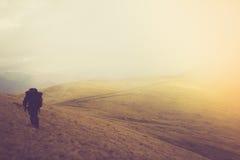 Turister med ryggsäckar klättrar till överkanten av berget i dimma Royaltyfri Bild