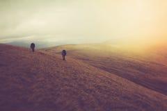 Turister med ryggsäckar klättrar till överkanten av berget i dimma Royaltyfria Bilder