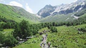 Turister med ryggsäcken som korsar stenig terräng med gräs på den soliga dagen Bästa sikt av turister i bergen på ett soligt stock video