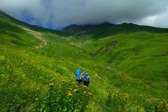 Turister med stora ryggsäckar reser i bergen på begreppet av bakgrund för livsstilsportklättringen Royaltyfri Foto