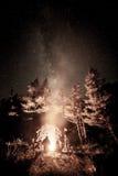 Turister nära en avfyra under stjärnorna Royaltyfria Bilder