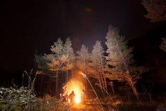 Turister nära en avfyra under stjärnorna Fotografering för Bildbyråer