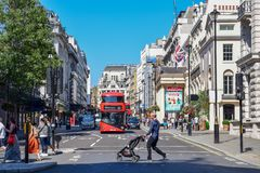 Turister och dubbeldäckarebuss i den London gatan på en Sunny Day royaltyfri bild