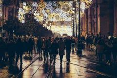 Turister och folk som går på julnatten i historisk mitt av Seville, Spanien royaltyfri bild