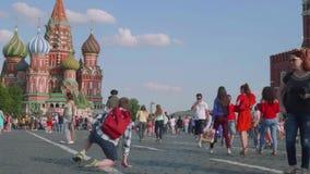 Turister och fotbollsfan går på röd fyrkant i moscow grabben gör fotosammanträde på knä arkivfilmer