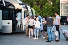 Turister och handboken nära bussar att stoppa nära flygplats i mötepunkt av handelsresande i Turkiet royaltyfri bild