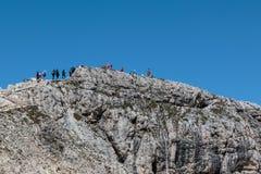 Turister och klättrare som går i stenbana bland karga berg i italienska Dolomitesfjällängar i sommar Tid Arkivbild