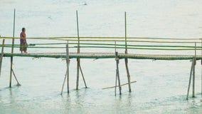 Turister och lokaler använder en liten bambubro över floden stock video
