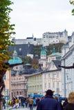 Turister och lokaler går till och med gatorna, Salzburg, Österrike royaltyfri foto
