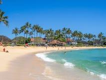 Turister och lokaler tycker om den Poipu stranden royaltyfria bilder