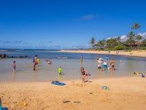 Turister och lokaler tycker om den Poipu stranden, Kauai Royaltyfri Foto