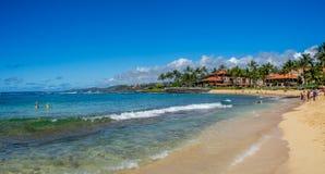 Turister och lokaler tycker om den Poipu stranden, Kauai Arkivfoto