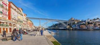 Turister och lokaler tycker om det Ribeira områdeslandskapet och solen i den Douro flodbanken nära Dom Luis som jag överbryggar Royaltyfri Bild