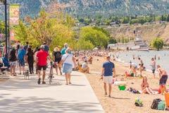 Turister och lokaler tycker om stranden och gångbanan på en sommareftermiddag arkivfoton
