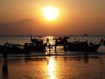Turister och traditionellt thailändskt longtailfartyg på solnedgångbakgrund royaltyfria foton