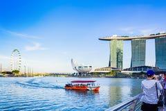 Turister på det Ducktour fartyget i Marina Bay och Marina Bay Sands Royaltyfri Foto