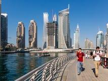 Turister på Dubaien Marina Walk promenerar i Mars arkivfoto