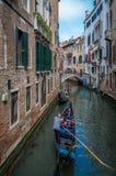 Turister på en gondol på kanalen av Venedig royaltyfri foto