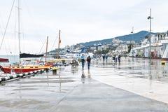 Turister på invallning i den Yalta staden i regnig dag Arkivfoto