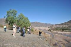 Turister på kusten av en bergflod i Altiplanoen Arkivbild