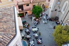 Turister på matställen i den huvudsakliga fyrkanten av Castelmola royaltyfri foto