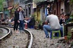 Turister på och bredvid köra för järnvägsspår begränsar bredvid hus i Hanoi arkivfoton
