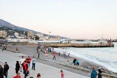 Turister på Pebble Beach av den Yalta staden i afton Arkivbilder