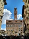 Turister på piazzadellaen Signoria, med Palazzo Vecchio i bakgrunden royaltyfri foto