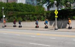 Turister på seagways som rider till och med en gata av Chicago arkivfoton
