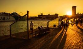 Turister på solnedgången, Rambla Del Mar, Barcelona, Spanien Royaltyfri Bild