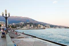 Turister på strand i den Yalta staden i afton Fotografering för Bildbyråer