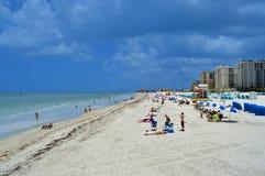 Turister på stranden som tycker om solen Arkivfoto