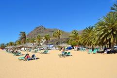 Turister på stranden som tycker om solen Royaltyfri Bild