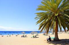 Turister på stranden som tycker om solen Royaltyfri Fotografi