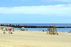Turister på stranden som tycker om solen Arkivbilder