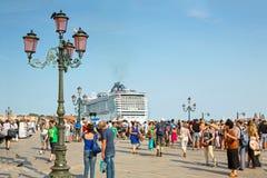 Turister på Sts Mark fyrkant i Venedig och kryssningskepp MSC Preziosa Royaltyfri Fotografi