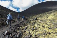 Turister på utfärder som är bitvis av att fotvandra slingan, klättrar till för den Tolbachik för det norr genombrottet det stora  Arkivfoto